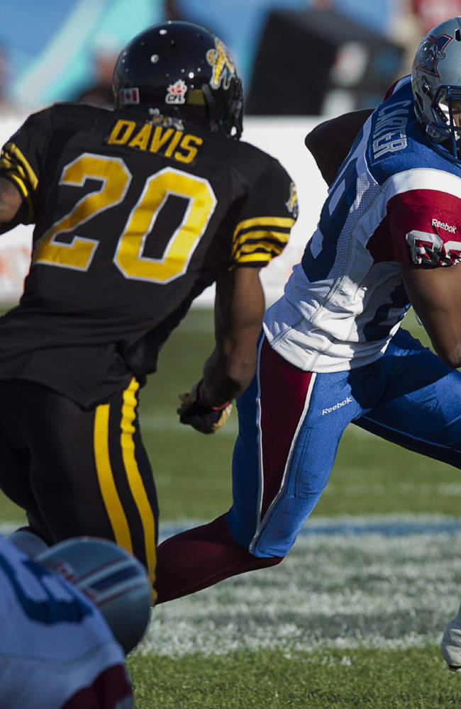 Montreal Alouettes' Duron Carter, right, runs around Hamilton Tiger-Cats' Emanuel Davis during the first half of a Canadian Football League game in Moncton, New Brunswick, on Saturday, Sept. 21, 2013