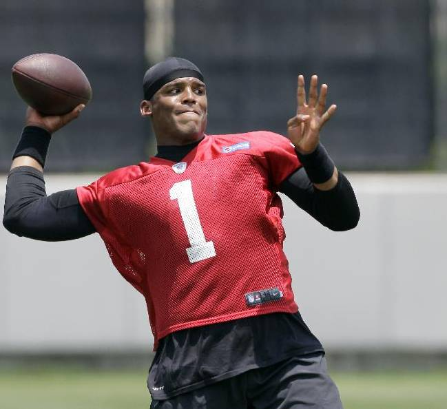 Carolina Panthers' quarterback Cam Newton (1) eyes a receiver during an NFL football organized team activity in Charlotte, N.C., Wednesday, May 28, 2014