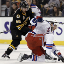 New York Rangers' Benoit Pouliot tries to swat the puck as Boston Bruins' David Krejci (46) of the Czech Republic, skaetes in during the second period of Boston's 3-2 win in a NHL hockey game in Boston Friday, Nov. 29, 2013 The Associated Press