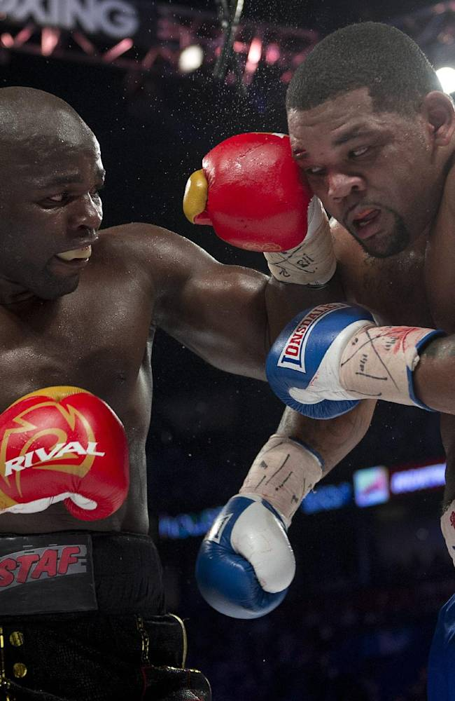 Mike Perez, right, from Cuba, takes a left to the head from Carlos Takam, from Cameroon, during their heavyweight boxing match on Saturday, Jan. 18, 2014, in Montreal. The fight ended in a majority draw