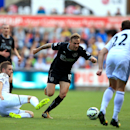 Swansea City's Gylfi Sigurdsson, left, slides in on Burnley's Matthew Taylor during the English Premier League match at the Liberty Stadium, Swansea, Wales, Saturday Aug. 23, 2014