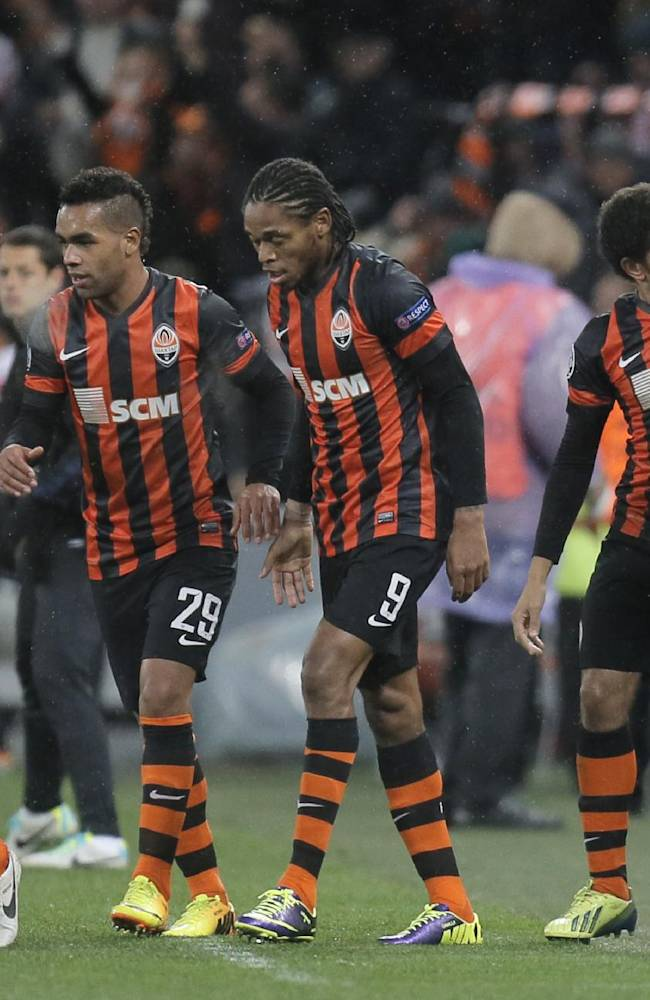 Shakhtar Donetsk's Taison, second right, celebrates with coach Mircea Lucescu,right, after he scores the  goal of the game for his side during their Champions League Group A soccer match against  Manchester United at Donbass Arena Stadium in Donetsk, Ukraine, Wednesday, Oct. 2, 2013
