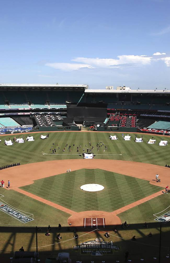 Pre-game entertainers rehears and ground crew put finishing touches on the field as preparations are made for the Major League Baseball opening game between the Los Angeles Dodgers and the Arizona Diamondbacks at the Sydney Cricket ground in Sydney, Saturday, March 22, 2014