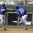Kansas City Royals' Justin Maxwell runs to third on a hit by Danny Valencia during the fourth inning of a spring exhibition baseball game Tuesday, March 11, 2014, in Suprise, Ariz. Los Angeles Dodgers' Chone Figgins watches the play The Associated Press