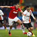 Manchester United's Rio Ferdinand, left goes to tackle Donetsk's Alex Teixeira during their Champions League group A soccer match between Manchester United and Shakhtar Donetsk at Old Trafford Stadium, Manchester, England, Tuesday, Dec. 10, 2013