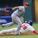 Philadelphia Phillies' Chase Utley, bottom, steals second as the throw from Cincinnati Reds catcher Ryan Hanigan gets past shortstop Cesar Izturis, top, during the sixth inning of a baseball game on Sunday, May 19, 2013, in Philadelphia. The Phillies won 3-2. (AP Photo/Tom Mihalek)