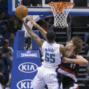 Orlando Magic's E'Twaun Moore (55) shoots the ball as Portland Trail Blazers' Robin Lopez (42) tries to block the shot during the second half of an NBA basketball game in Orlando, Fla., Tuesday, March 25, 2014 The Associated Press