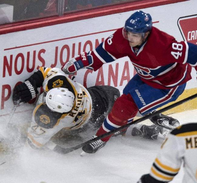 Boston Bruins' Torey Krug crashesinto the boards in front of Montreal Canadiens' Daniel Briere during first period NHL hockey action Wednesday, March 12, 2014 in Montreal