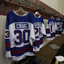 The jersey of goalie Jim Craig from the 1980 U.S. Olympic ice hockey team hangs in a locker room at Herb Brooks Arena on Saturday, Feb. 21, 2015, in Lake Placid, N.Y. Thirty-five years after the team's stunning gold medal at the 1980 Lake Placid Winter Olympics, the once-fuzzy-faced heroes are being feted for their signature accomplishment. Every surviving member of the hockey team is back for a reunion at Herb Brooks Arena, the hockey rink on Main Street they made famous with one of the most memorable upsets in sports history. (AP Photo/Mike Groll)
