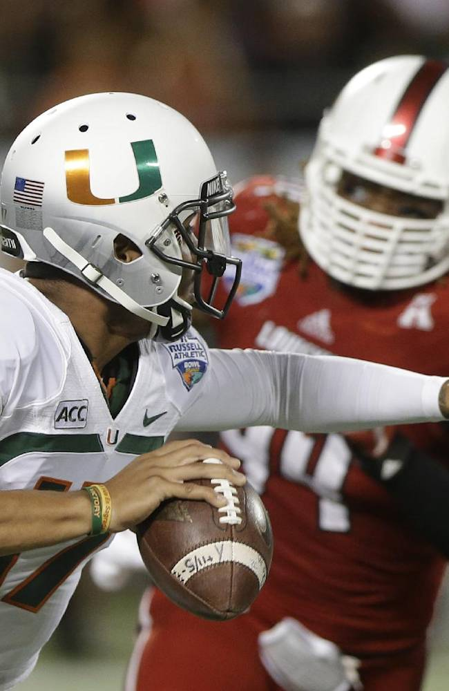 Miami quarterback Stephen Morris (17) scrambles away from Louisville defensive end Lorenzo Mauldin during the first half of the Russell Athletic Bowl NCAA college football game in Orlando, Fla., Saturday, Dec. 28, 2013