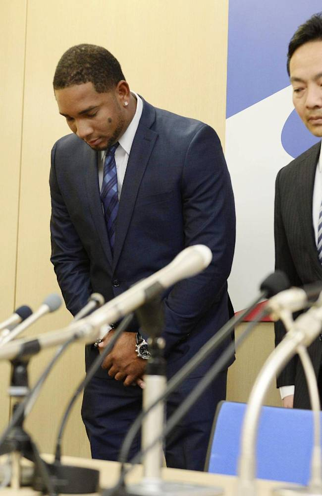 Yakult Swallows slugger Wladimir Balentien, center, bows during a press conference in Tokyo Wednesday, Jan. 29, 2014. Balentien has apologized to his fans, several days after pleading not guilty to domestic violence charges in Florida. As is the custom in Japan, Balentien bowed deeply and then apologized Wednesday to his fans and teammates for the actions that led to his arrest on Jan. 13