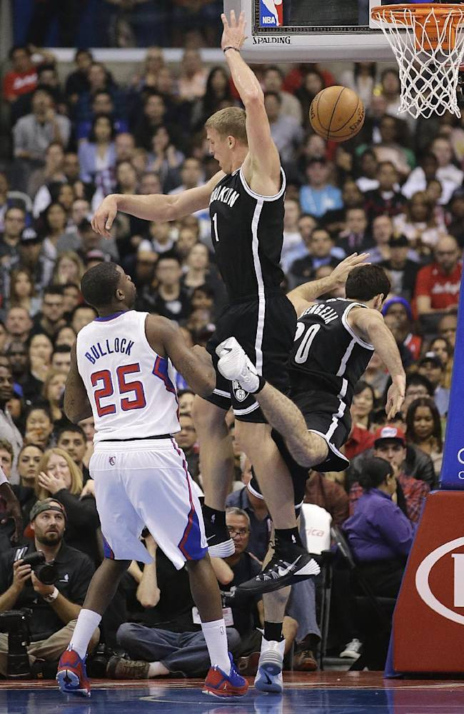 Brooklyn Nets' Mason Plumlee, center, jumps for a rebound after Tornike Shengelia, right, of Georgia, missed the shot during the first half of an NBA basketball game against the Los Angeles Clippers on Saturday, Nov. 16, 2013, in Los Angeles. Los Angeles Clippers' Reggie Bullock watches at left