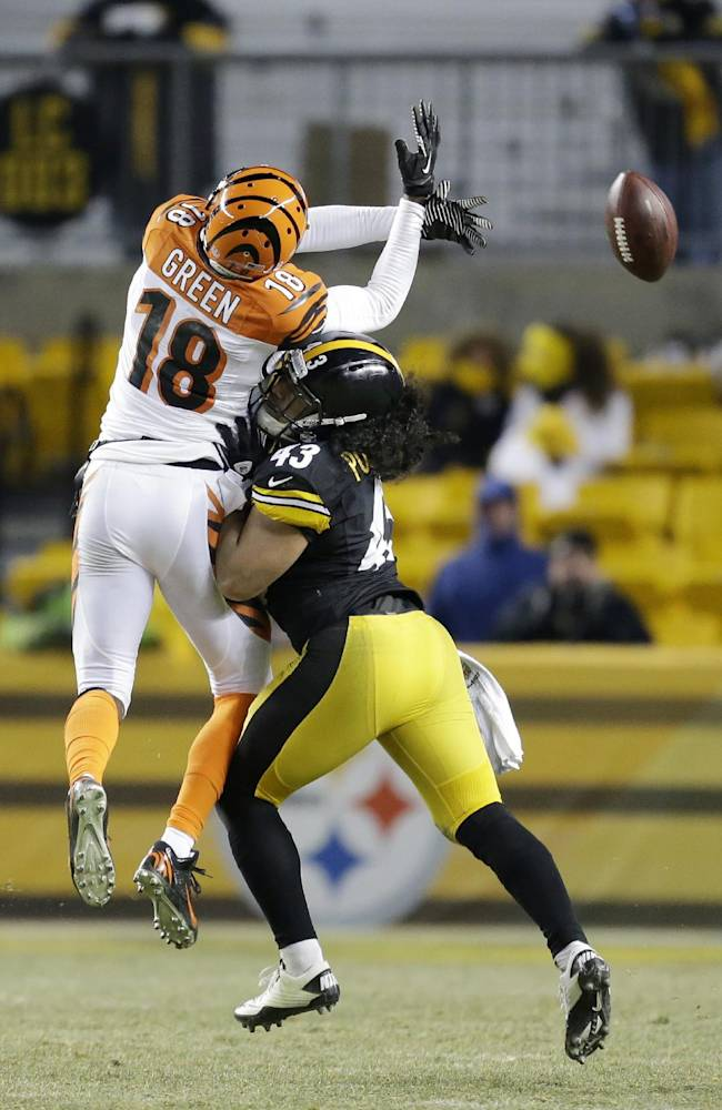 Cincinnati Bengals wide receiver A.J. Green (18) can't hang onto a pass as he is hit by Pittsburgh Steelers strong safety Troy Polamalu (43) during the fourth quarter of  an NFL football game in Pittsburgh, Sunday, Dec. 15, 2013. The Steelers won 30-20