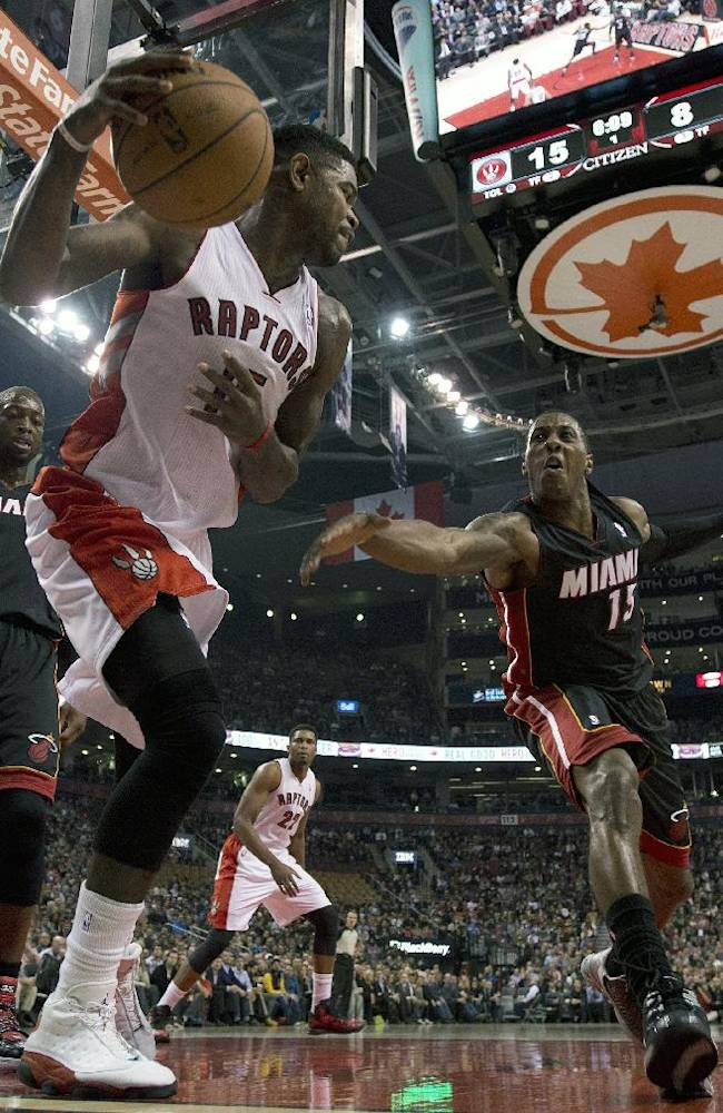 Toronto Raptors forward Amir Johnson, center, rebounds against Miami Heat guards Mario Chalmers, right, and Dwyane Wade, left, during the first half of an NBA basketball game, Tuesday, Nov. 5, 2013 in Toronto