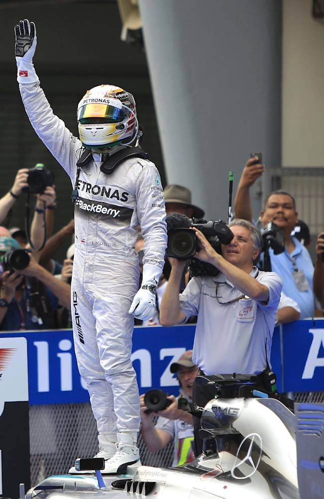 Mercedes driver Lewis Hamilton of Britain waves after winning the Malaysian Formula One Grand Prix at Sepang International Circuit in Sepang, Malaysia, Sunday, March 30, 2014