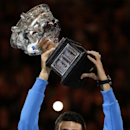 Novak Djokovic of Serbia lifts the trophy after defeating Andy Murray of Britain in the men's singles final at the Australian Open tennis championship in Melbourne, Australia, Sunday, Feb. 1, 2015. (AP Photo/Vincent Thian)