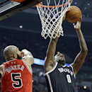 Brooklyn Nets center Andray Blatche, right, goes up for a shot against Chicago Bulls forward Carlos Boozer during the first half of an NBA basketball game in Chicago on Thursday, Feb. 13, 2014 The Associated Press