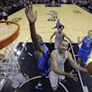 San Antonio Spurs' Tony Parker (9), of France, is defended by Dallas Mavericks' Samuel Dalembert (1) as he drives to score during the second half of an NBA basketball game, Sunday, March 2, 2014, in San Antonio. San Antonio won 112-106 The Associated Pres