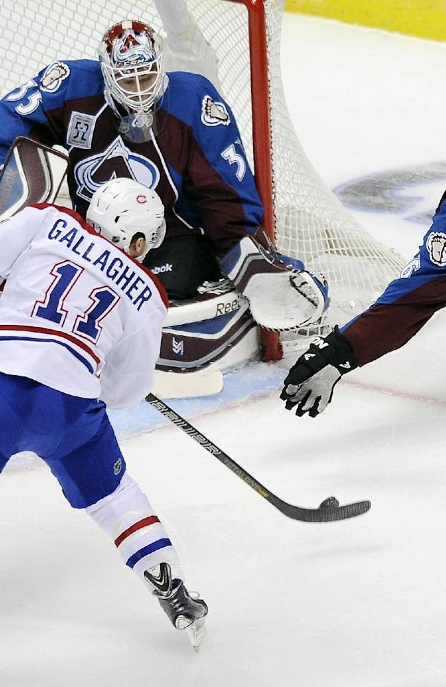 Colorado Avalanche defenseman Erik Johnson, right, tries to block a shot by Montreal Canadiens right wing Brendan Gallagher, left, against Avalanche goalie Jean-Sebastien Giguere, top center, in the first period of an NHL hockey game on Saturday, Nov. 2, 2013, in Denver. The Avalanche won 4-1