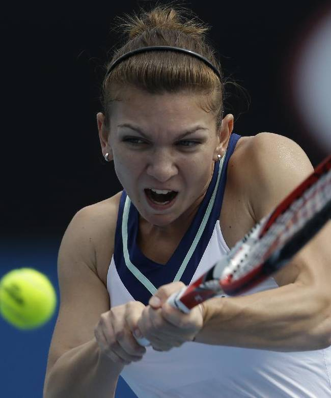 Simona Halep of Romania makes a backhand return to Zarina Diyas of Kazakhstan during their third round match at the Australian Open tennis championship in Melbourne, Australia, Saturday, Jan. 18, 2014