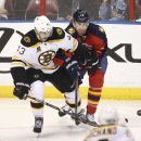 Boston Bruins' Matt Bartkowski (43) and Florida Panthers' Jimmy Hayes (12) chase the puck during the third period of an NHL hockey game in Sunrise, Fla., Sunday, March 9, 2014. Boston won 5-2 The Associated Press