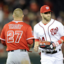 Washington Nationals left fielder Bryce Harper (34) runs from the field past Los Angeles Angels' Mike Trout (27) during the middle of the seventh inning of a baseball game, Monday, April 21, 2014, in Washington. The Angels won 4-2 The Associated Press