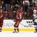 Arizona Coyotes' Antoine Vermette, left, celebrates his goal with teammate Lauri Korpikoski (28), of Finland, as Colorado Avalanche's Gabriel Landeskog (92), of Sweden, skates by during the first period of an NHL hockey game Tuesday, Nov. 25, 2014, in Gle