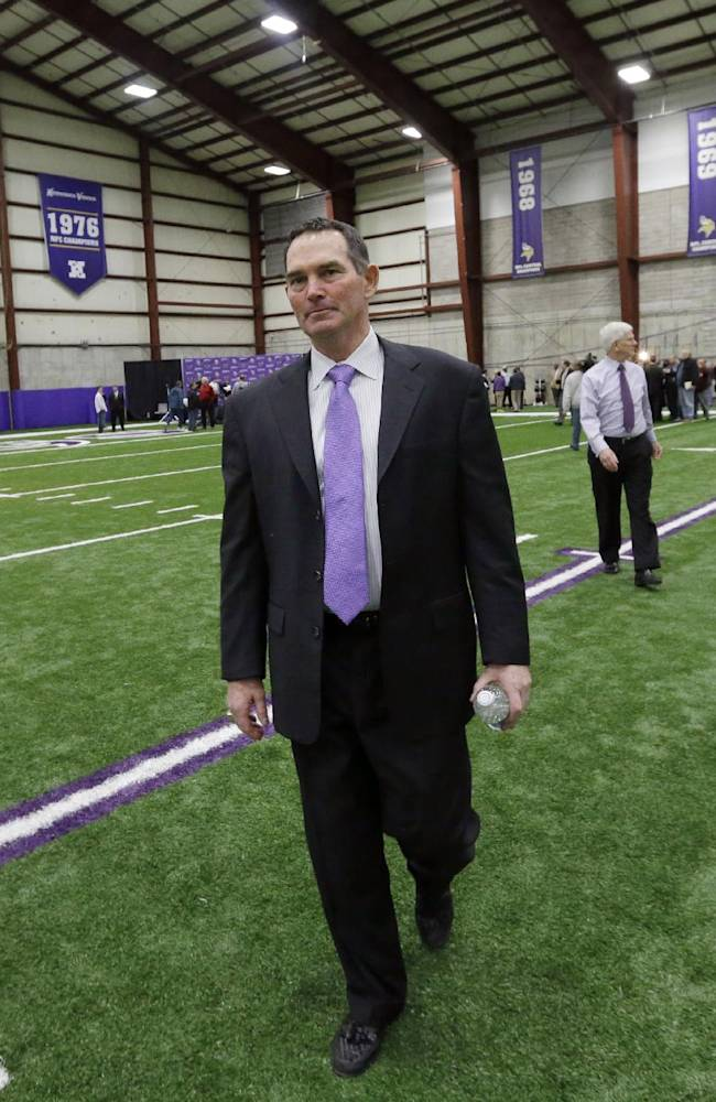 New Minnesota Vikings head coach Mike Zimmer walks across the practice field during an NFL football media availability at Winter Park in Eden Prairie, Minn., Friday, Jan. 17, 2014
