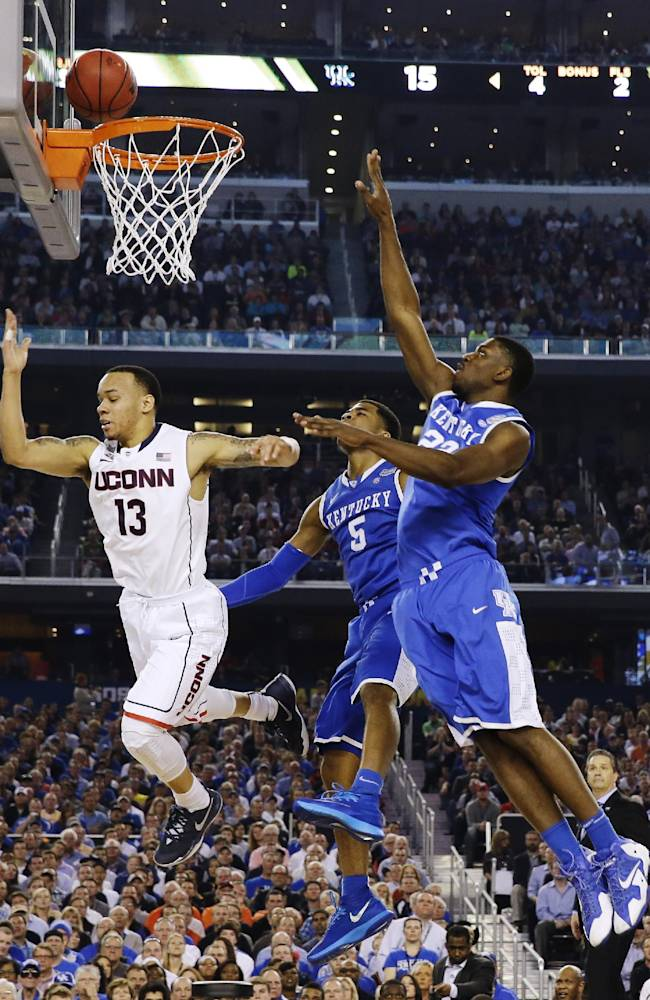 Connecticut guard Shabazz Napier (13) puts up the ball against Kentucky guard Andrew Harrison (5) and forward Alex Poythress (22) during the first half of the NCAA Final Four tournament college basketball championship game Monday, April 7, 2014, in Arlington, Texas