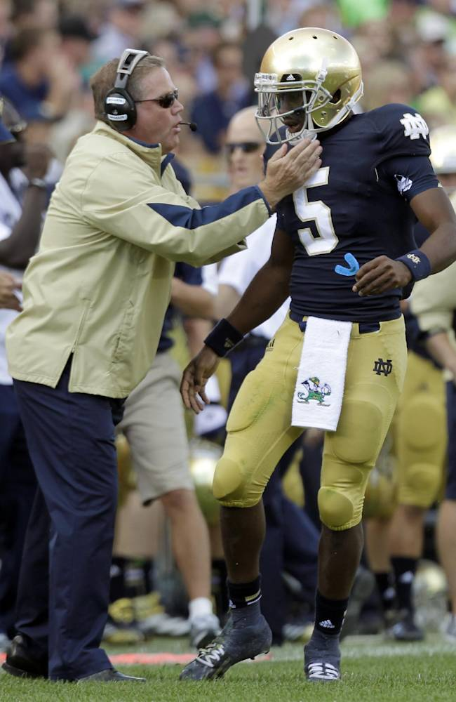 Notre Dame coach Brian Kelly, left, gives a play to quarterback Everett Golson during the first half of an NCAA college football game against Purdue in South Bend, Ind., Saturday, Sept. 8, 2012