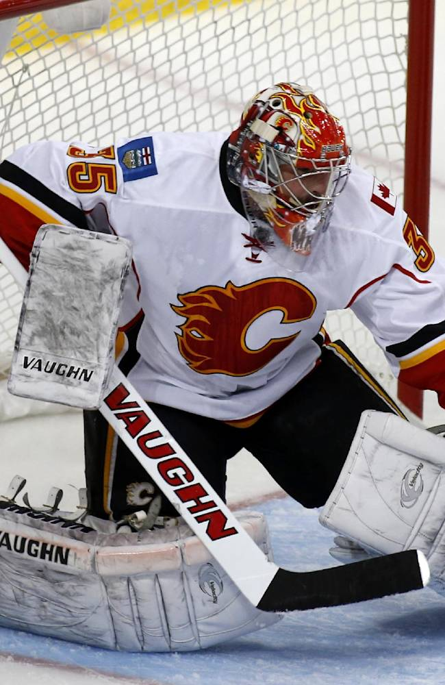 Calgary Flames goalie Joey MacDonald (35) makes a save in the first period of an NHL hockey game against the Dallas Stars, Friday, March 14, 2014, in Dallas