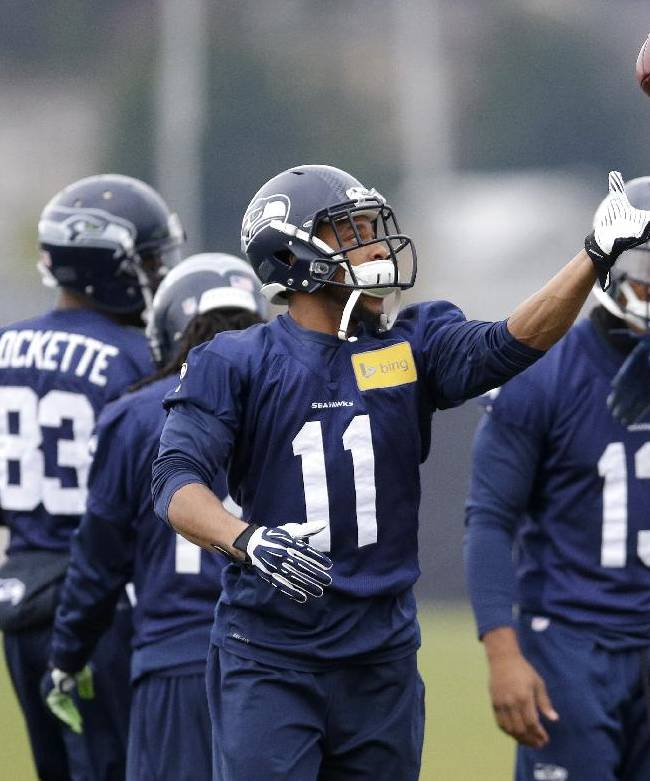Seattle Seahawks wide receiver Percy Harvin (11) catches a football tossed to him during stretching warmups, Thursday, Jan. 2, 2014, before NFL practice in Renton, Wash., as he stands with wide receiver Ricardo Lockette (83) and practice squad wide receiver Phil Bates (13)