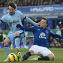 Manchester City's David Silva, left, fends off tackle by Everton's Muhamed Besic during the English Premier League soccer match between Everton and Manchester City at Goodison Park Stadium, Liverpool, England, Saturday Jan. 10, 2015