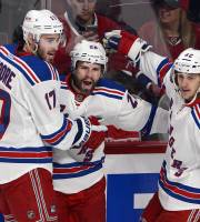 New York Rangers right wing Martin St. Louis (26) celebrates with teammates John Moore and Carl Hagelin after scoring against the Montreal Canadiens during the first period in Game 1 of the Eastern Conference finals in the NHL hockey Stanley Cup playoffs in Montreal on Saturday, May 17, 2014. The Rangers won 7-2. (AP Photo/The Canadian Press, Ryan Remiorz)