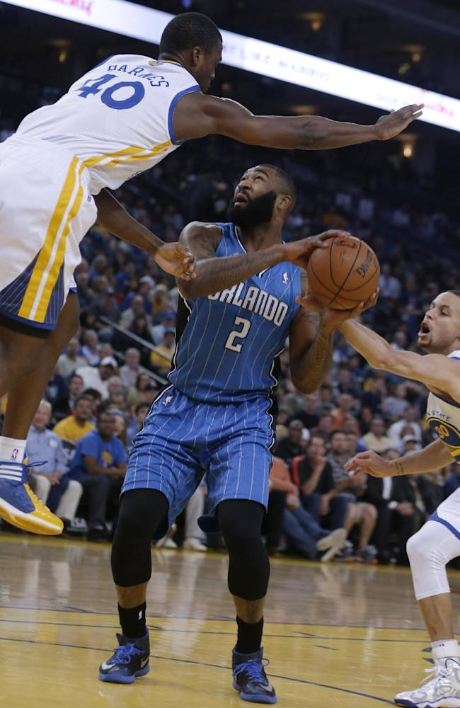 Orlando Magic forward Kyle O'Quinn, center, attempts a shot between Golden State Warriors' Harrison Barnes, left, and Stephen Curry during the first half of an NBA basketball game Tuesday, March 18, 2014, in Oakland, Calif