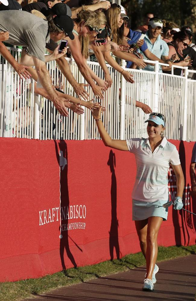 Lexi Thompson greets fans on her way to 18th green in the final round of the Kraft Nabisco Championship golf tournament Sunday, April 6, 2014, in Rancho Mirage, Calif. Thompson defeated Michelle Wie by three strokes to take the win. AP Photo/Chris Carlson)