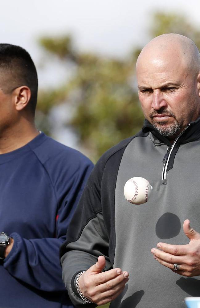 Atlanta Braves bullpen coach Eddie Perez, left, stands with manager Fredi Gonzalez during a spring training baseball workout, Thursday, Feb. 13, 2014, in Kissimmee, Fla