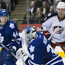 Toronto Maple Leafs goaltender James Reimer, center, makes a save as Leafs' Morgan Reilly, left, and Columbus Blue Jackets RJ Umberger stands near during the third period of an NHL hockey game in Toronto on Monday, March 3, 2014 The Associated Press