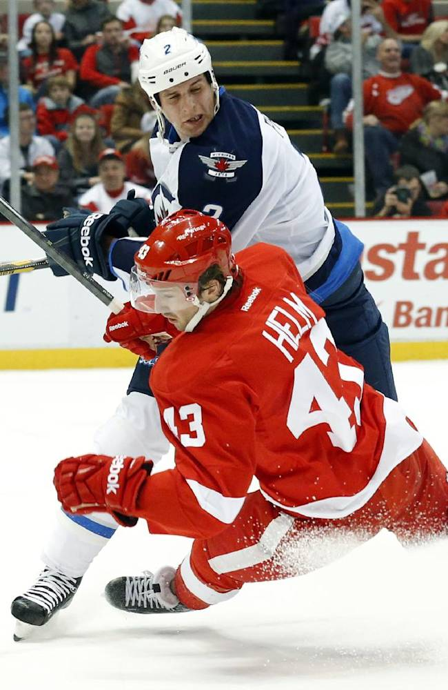 Winnipeg Jets defenseman Adam Pardy (2) checks Detroit Red Wings center Darren Helm (43) during the second period of an NHL hockey game in Detroit, Tuesday, Nov. 12, 2013