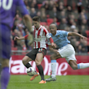 Sunderland's Fabio Borini, centre, gets away from Manchester City's Vincent Kompany on his way to scoring during the League Cup Final at Wembley Stadium, London, England, Sunday March 2, 2014