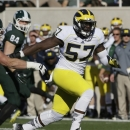 FILE - This Oct. 25, 2014, file photo shows Michigan defensive end Frank Clark (57) breaking through the Michigan State line during the first half of an NCAA college football game in East Lansing, Mich. Defensive end Frank Clark has been dismissed from the Michigan football team after being accused of domestic violence in Ohio over the weekend. The 21-year-old Clark pleaded not guilty Monday, Nov. 17, 2014, to charges of assault and domestic violence. (AP Photo/Carlos Osorio, File)