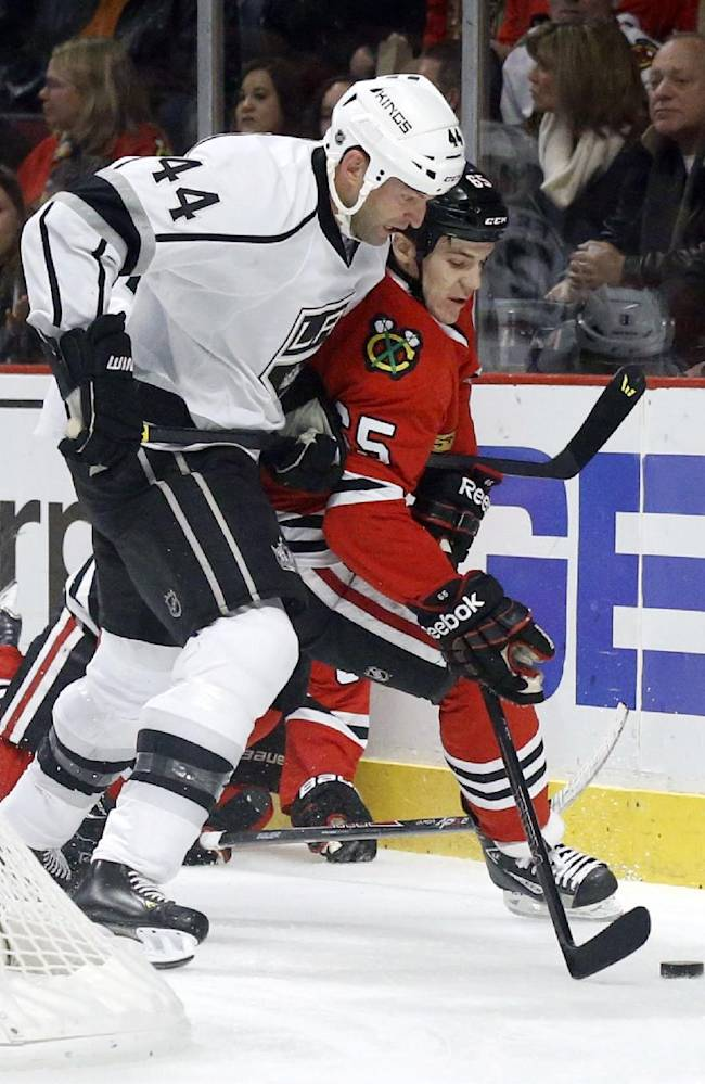 Los Angeles Kings defenseman Robyn Regehr (44) battles Chicago Blackhawks center Andrew Shaw for a loose puck during the second period of an NHL hockey game Monday, Dec. 30, 2013, in Chicago