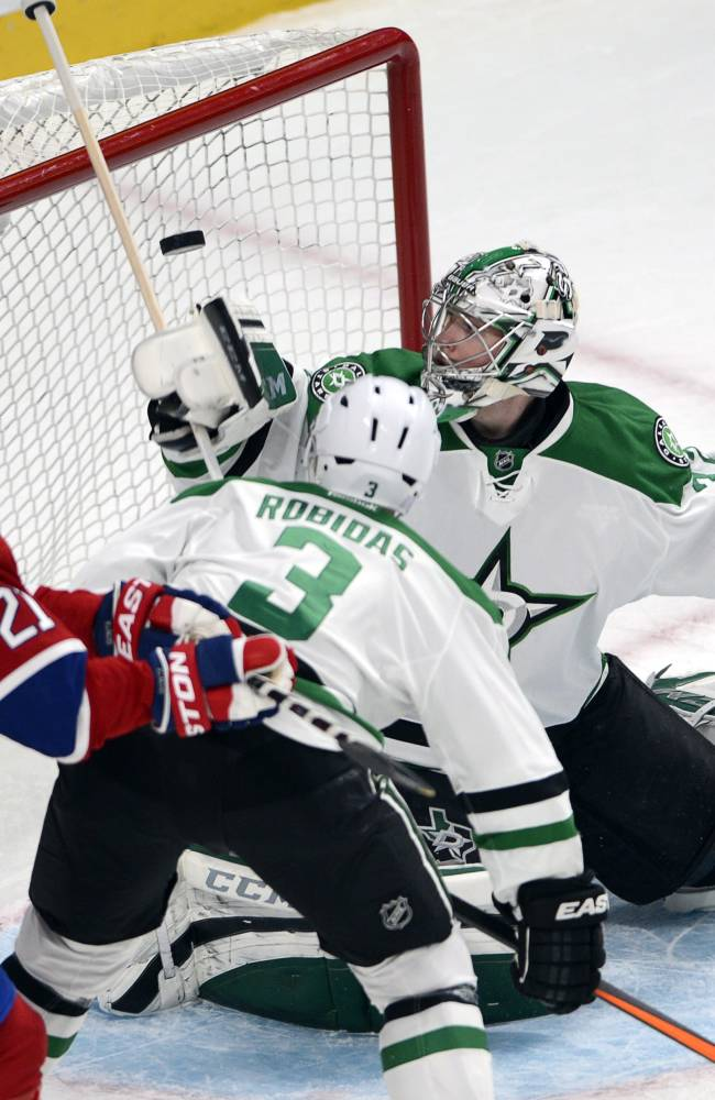 Dallas Stars goalie Kari Lehtonen (32) lets in a goal as Canadiens right wing Brian Gionta (21) and Dallas Stars defenseman Stephane Robidas (3) watch during the first period of an NHL hockey game Tuesday, Oct. 29, 2013, in Montreal