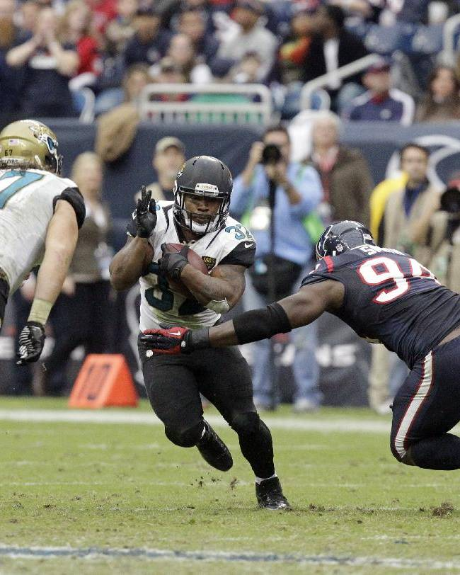 Jacksonville Jaguars running back Maurice Jones-Drew (32) tries to maneuver around Houston Texans defensive end Antonio Smith (94) during the fourth quarter of an NFL football game Sunday, Nov. 24, 2013, in Houston