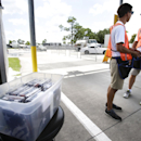 Ticket takers stand by a box containing American flags, left, to hand out to race fans that request one in exchange for a Confederate flag at the entrance to Daytona International Speedway for this weekends races, Friday, July 3, 2015, in Daytona Beach, Fla. (AP Photo/John Raoux)