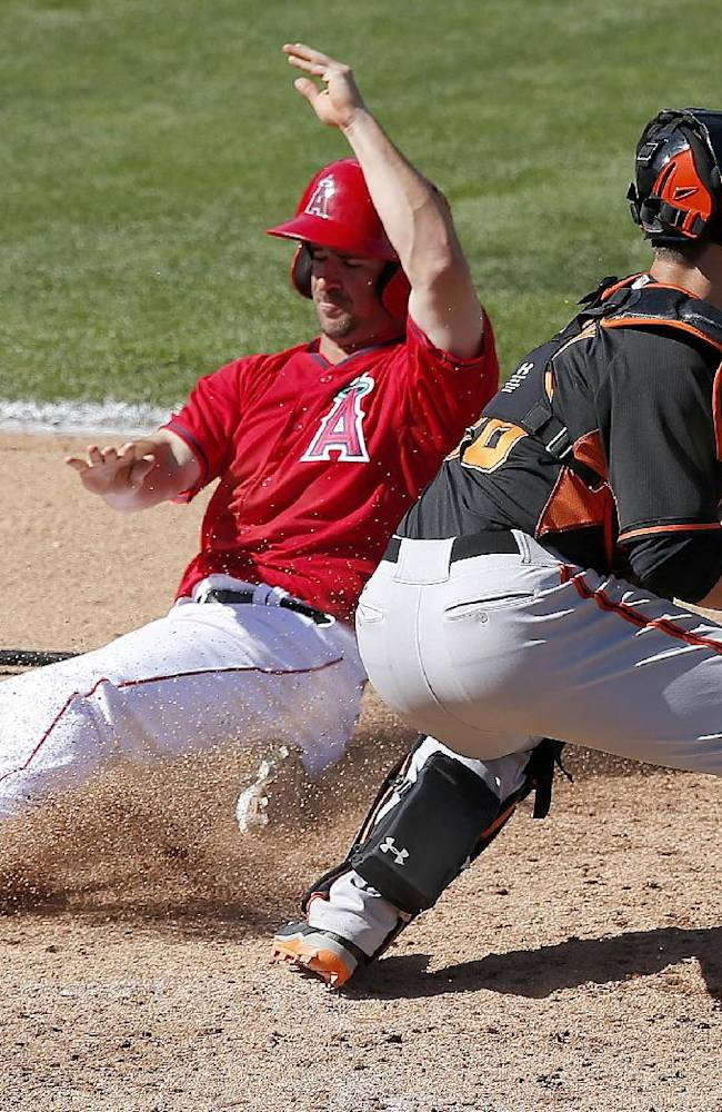 Los Angeles Angels' Drew Heid, left, scores ahead of the tag by San Francisco Giants' Buster Posey, right, in the sixth inning of a spring training baseball game, Monday, March 17, 2014, in Tempe, Ariz.  The Angels defeated the Giants 8-7