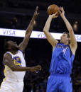 Dallas Mavericks' Dirk Nowitzki, right, shoots over Golden State Warriors' Draymond Green during the first half of an NBA basketball game on Wednesday, Dec. 11, 2013, in Oakland, Calif. (AP Photo/Ben Margot)