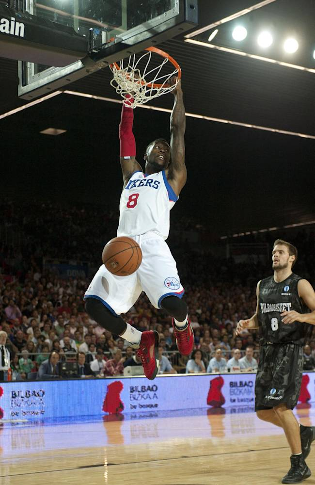 Philadelphia's 76ers Tony Wroten, left, dunks while Bilbao Basket's Fran Pilepic of Croatia, right, looks on during the NBA Global basketball game in Bilbao northern Spain on Sunday, Oct. 6, 2013