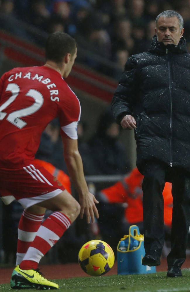 Chelsea's manager Jose Mourinho, right, kicks the ball back to Southampton's Calum Chambers during their English Premier League soccer match at St Mary's stadium, Southampton, England, Wednesday, Jan. 1, 2014