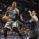San Antonio Spurs guard Danny Green, left, looks to pass around Orlando Magic center Nikola Vucevic during the first half on an NBA basketball game on Saturday, March 8, 2014, in San Antonio The Associated Press
